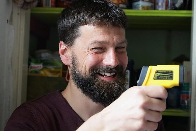Praxistester Dr. Heiko Stemmann misst die Temperatur seiner Wände.