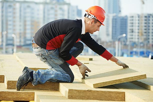 Das Foto zeigt einen Handwerker beim Dämmen eines Flachdaches.
