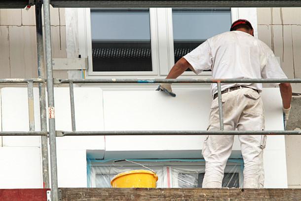 Fassadendämmung: Auf dem Bild ist ein Mann auf einem Gerüst.