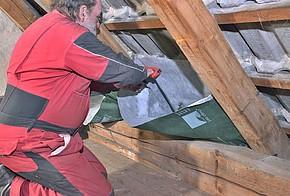 Handwerker befestigt Dämmsack an der Dachschräge.