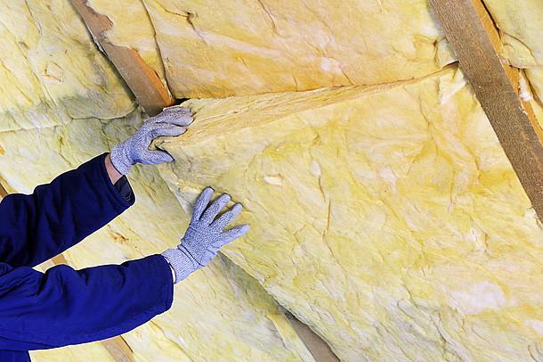 Auf dem Foto ist das Anbringen der Dachplatten zu sehen.