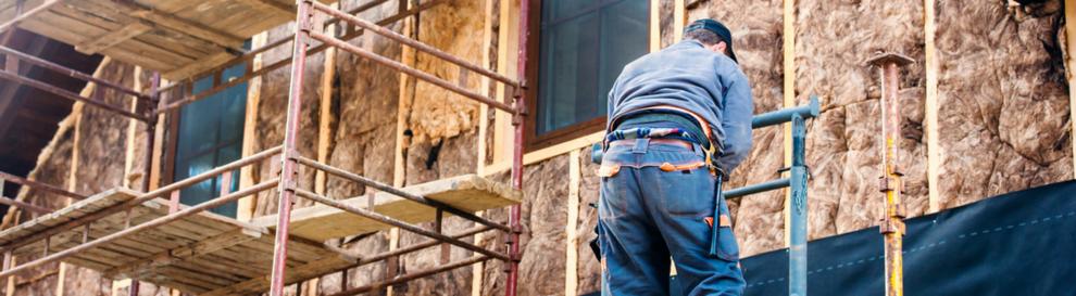 Handwerker auf dem Baugerüst vor einer gedämmten Fassade.